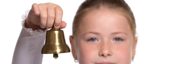 Young school girl ringing a golden bell on white background focu