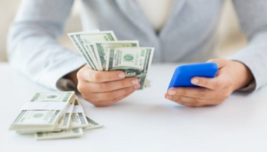 close-up-of-woman-hands-with-smartphone-and-money_sizeXS.jpg