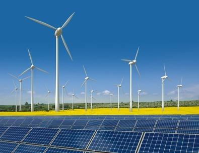 Windkrafträder und Solarmodule in einem Rapsfeld