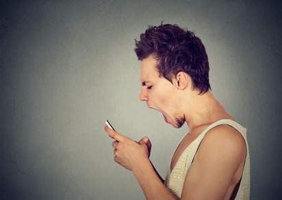 Side profile portrait angry young man screaming on mobile phone