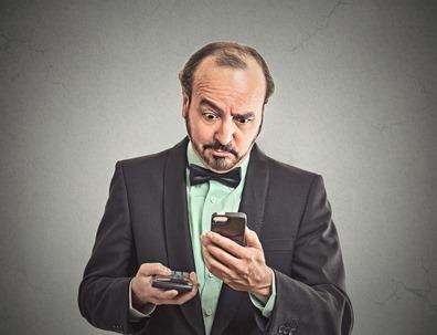 surprised businessman looking on smart phone holding calculator