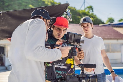 Steadicam operator and his assistant prepare camera and 3-axis stabilizer-gimbal for a commercial shoot