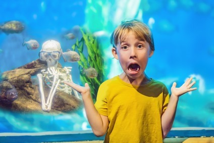 The boy got scared Skeleton and piranha in an aquarium
